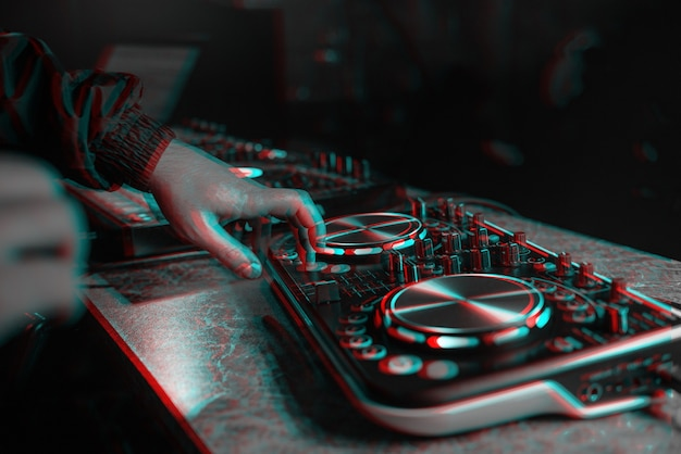 Dj console for mixing music with hands and with blurred people at a night club. black and white with 3d glitch virtual reality effect