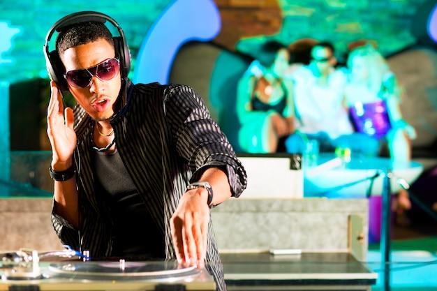 Dj in disco club, crowd background