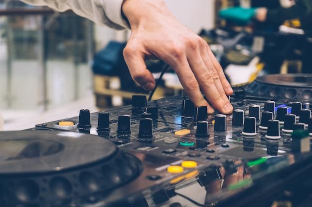 パフォーマンス上のdjコンソール(パーティー)。機器での音楽の作成とdjのチューニング