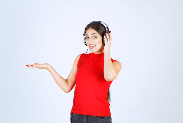 ヘッドフォンで何かを指したり、手に何かを見せたりした赤いシャツを着た dj の女の子。
