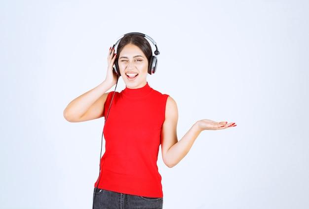 Dj девушка в красной рубашке с наушниками, указывая что-то или показывая что-то в руке.