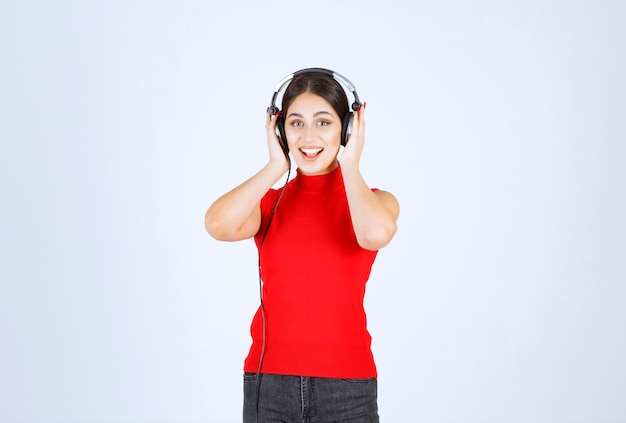 Dj girl in red shirt wearing headphones and listening to a good music.