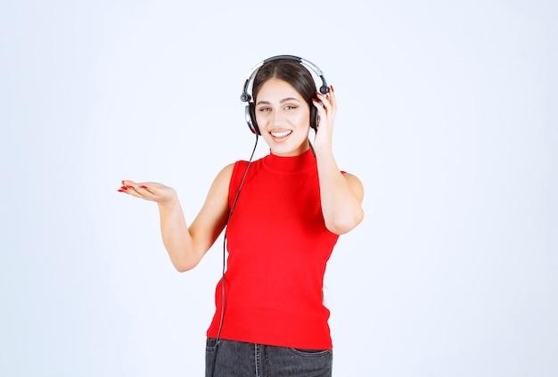 Ragazza del dj in camicia rossa con le cuffie che indica qualcosa o che mostra qualcosa in mano.