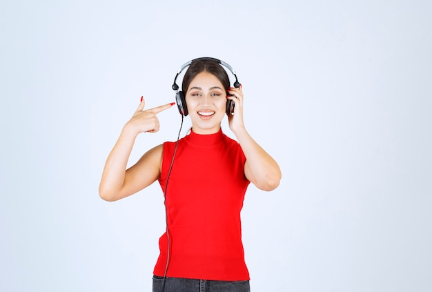 Dj girl with headphones pointing at it.