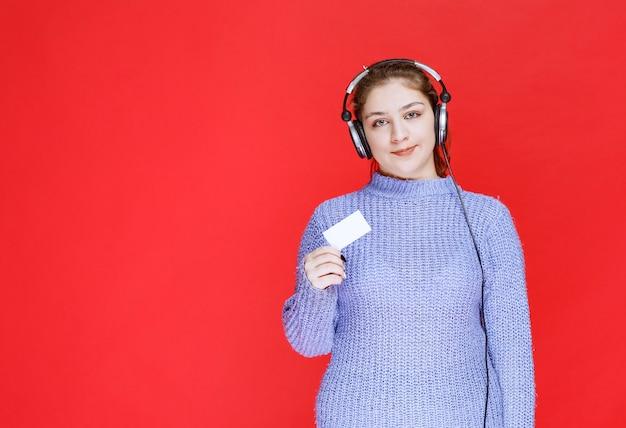 Девушка ди-джея с наушниками, представляя ее визитную карточку.