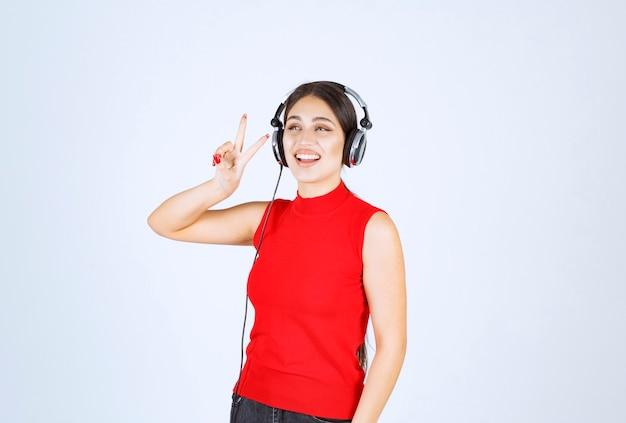平和と友情のメッセージを送信するヘッドフォンを持つ dj の女の子。