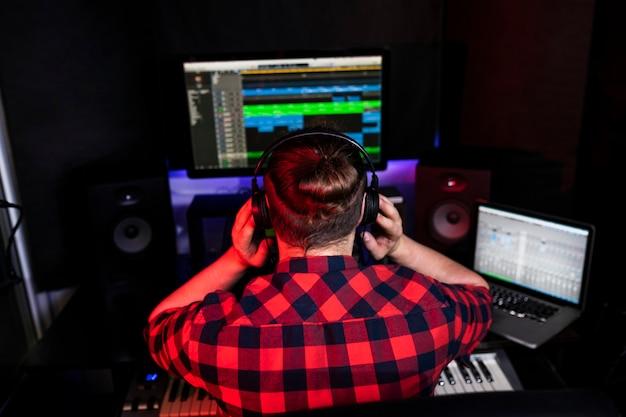 長い髪のdjの男は、スタジオで録音したばかりのステレオで彼の新しい曲を聴いています