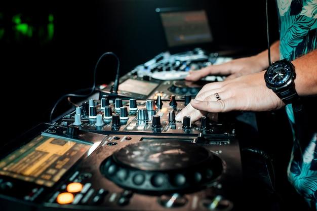 Dj hand mixes on a professional mixer controller at a concert