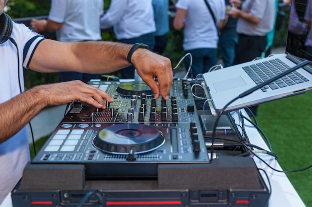 Dj hands on equipment. dj turntable console mixer controlling with two hand in concert