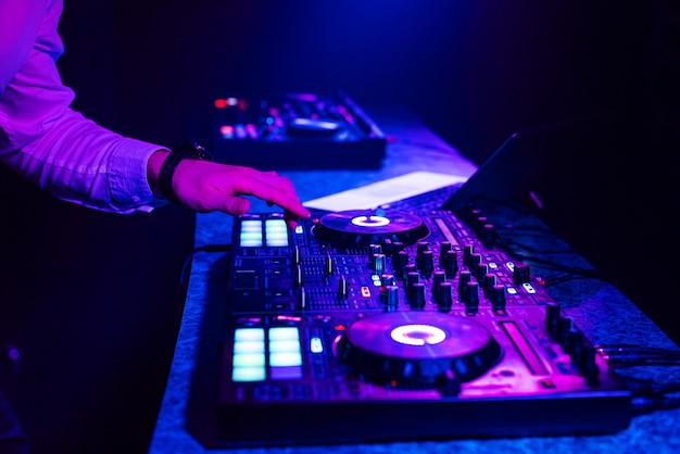 Dj hands mix music on a mixing board in a nightclub