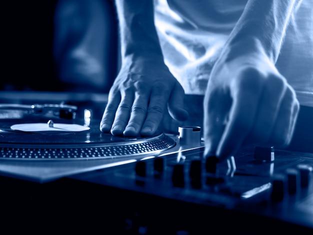 Djはプロの音楽機器デッキのビニールレコードのターンテーブルとタイムコード、2020年のトレンドの色、クラシックなブルーのトーンを手にしています