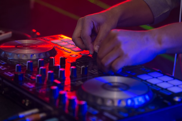 Dj hands on stage mixing, disc jockey and mix tracks on sound mixer controller, playing music at bar, disco tech or night club party.
