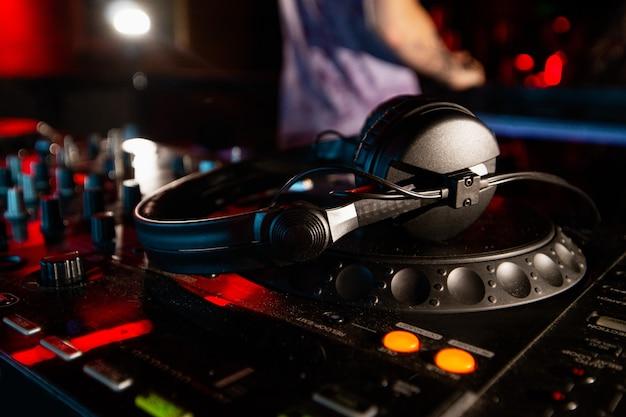 Dj가 음악 세션을 중단했습니다. 디스크 자키 콘솔 또는 턴테이블 위에 헤드폰을 얹은 사진을 닫습니다. 혼합 장비. 클럽 생활 개념.