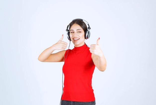 헤드폰을 착용하고 음악을 즐기는 빨간 셔츠에 dj.