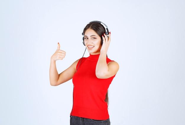 Dj в красной рубашке в наушниках и наслаждается музыкой.