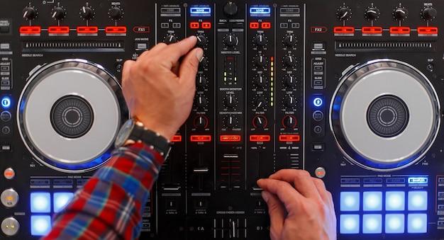 작업 과정에서 dj. 남자의 손은 믹싱 콘솔에서 재생됩니다. 평면도