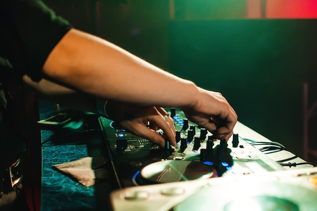Dj mix music hands in night club at event on mixer