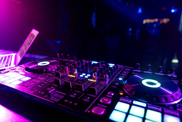 Dj mixer in the booth on the background of the nightclub dance floor