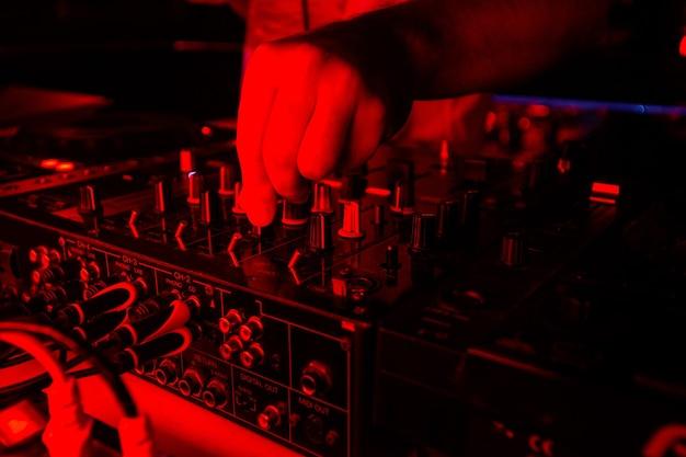 밝은 붉은 빛에 dj 믹서입니다. 디스크 자키 콘솔에서 텀블러를 돌리는 남성 손의 클로즈업 샷을 잘라냅니다. 유흥 개념입니다. 좋은 음악과 함께 파티에 열광하십시오.