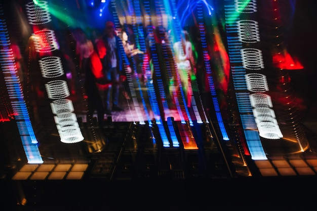 Dj mixer in a nightclub with glowing colored lights from controllers and buttons