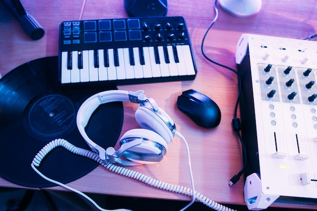 녹음 스튜디오 책상에 헤드폰과 신디사이저가있는 dj 믹서