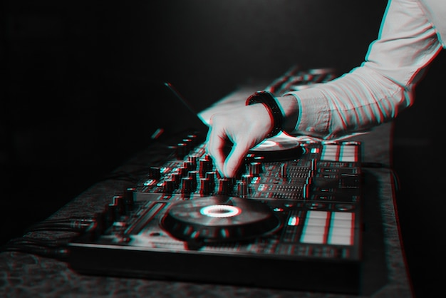 Dj mixes electronic music with his hands on a music controller board in a night club in a booth. black and white with 3d glitch virtual reality effect