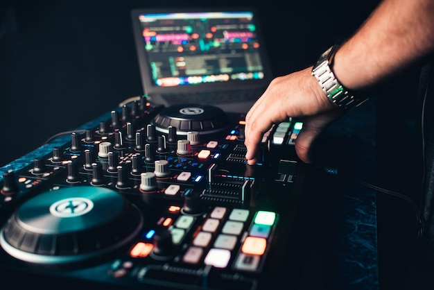 Dj mixes and manages music on professional contemporary music board