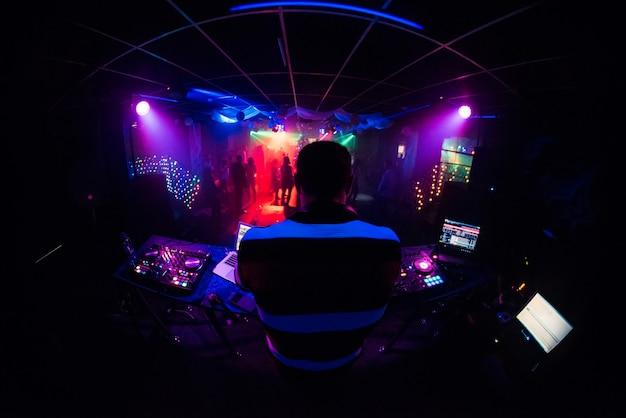 Dj mixes music in a nightclub with people dancing