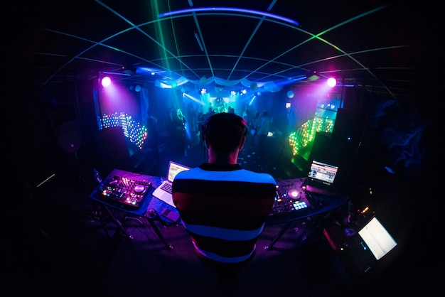 Dj mixes music in a nightclub with people dancing