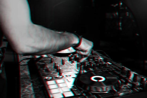 Djは、パーティーのナイトクラブでプロのコントローラーボードで音楽をミックスします。 3dグリッチ効果