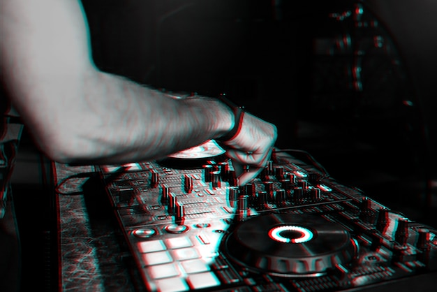 Dj mixes music on a professional controller board in a nightclub at a party. 3d glitch effect