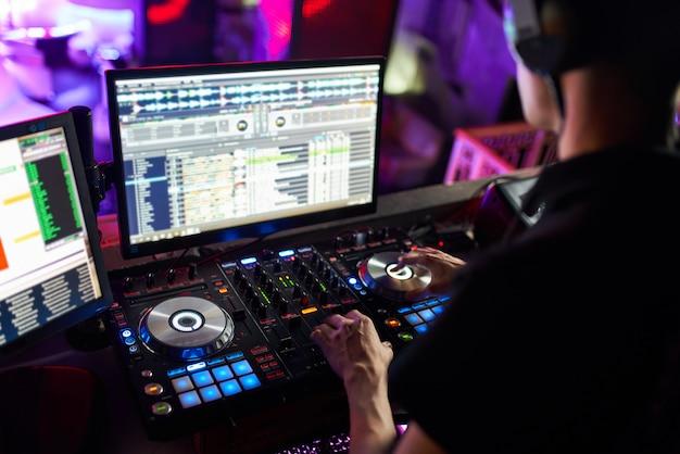 Dj смешивает трек в ночном клубе на вечеринке