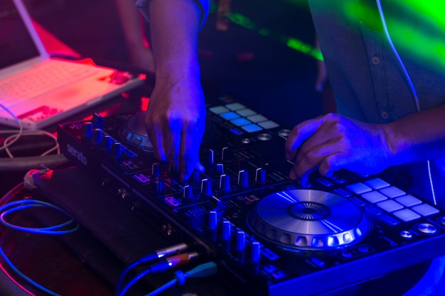 Dj mixing tracks on a mixer in a nightclub.