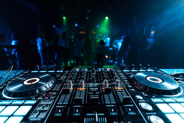 Dj music mixer in a booth in a nightclub on a blurred background of dancing people
