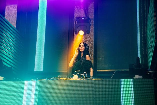 Dj на сцене в ночном клубе дискотеки микширования техно-музыки бит