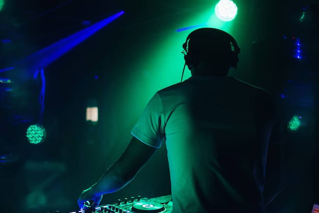 Dj performs in nightclub and plays music