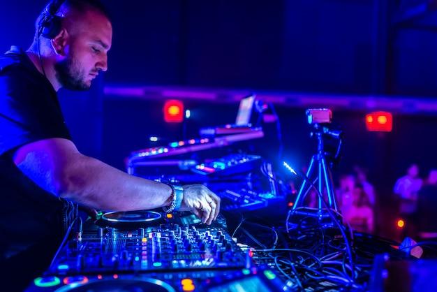 Dj, играющий хаус и техно музыку в ночном клубе