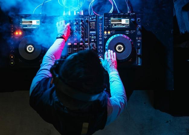 나이트 클럽에서 사운드 믹서에서 음악을 재생하는 dj