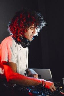 Dj играет музыку. уверенный молодой dj закручивая на поворотном столе, стоя изолированным.