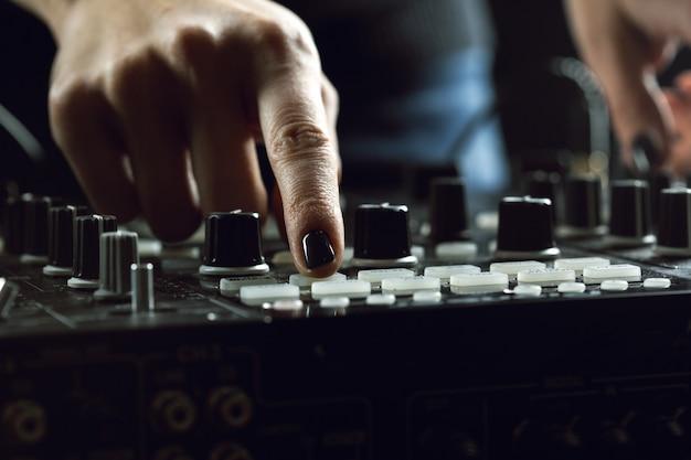 Dj playing music at mixer closeup