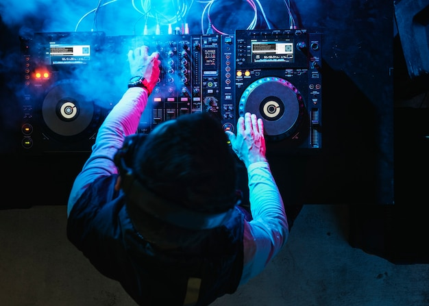 Dj playing music at sound mixer in night club