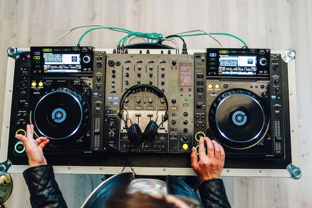 Dj plays on the best, famous cd players at nightclub during party.