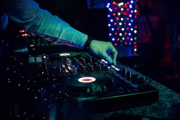 Dj plays electronic music in a nightclub at a party