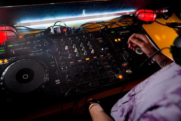 Dj는 나이트 클럽의 무대에서 턴테이블 콘솔에서 라이브 세트와 믹싱 음악을 재생합니다. 클럽 파티에서 사운드 믹서 스테이션에 디스크 조키 손. 음악 재생 및 파티를 위한 dj 믹서 컨트롤러 패널.