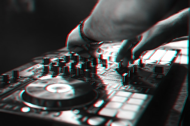 Dj plays music with his hands on a mixer controller at a live electronic music concert