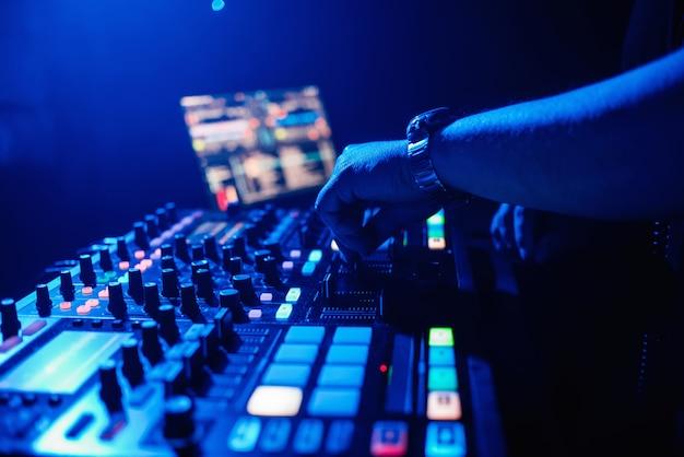 Dj играет на музыкальном микшере в ночном клубе