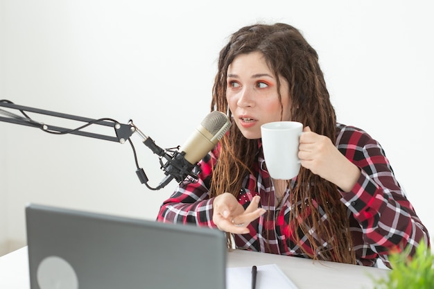Dj, radio host and blogging concept - young woman working at the studio