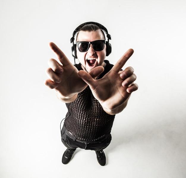Dj - рэпер в стильной футболке с наушниками и с поднятыми руками