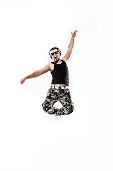 Dj-рэпер в наушниках берет рэп и танцует брейк-данс на свете