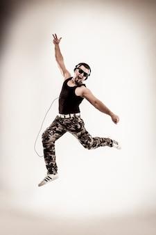 헤드폰을 쓴 dj 랩퍼가 랩과 브레이크 댄스 댄스를 취합니다.